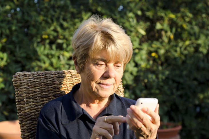 Retired Woman relaxing outdoor with her Smartphone